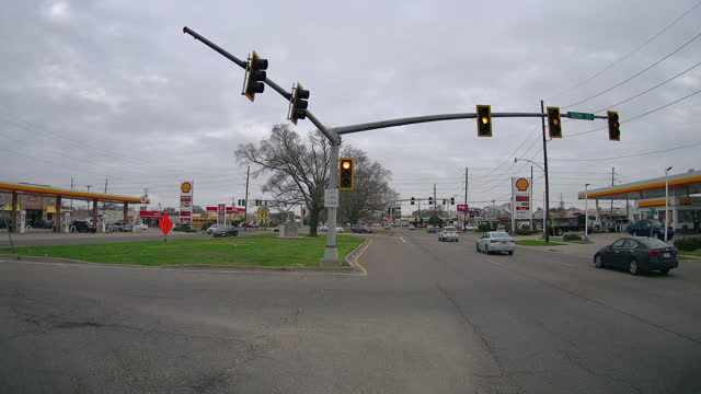 intersection traffic and two shell gas stations on both side of the street amid the coronavirus pandemic. - fast motion stock videos & royalty-free footage