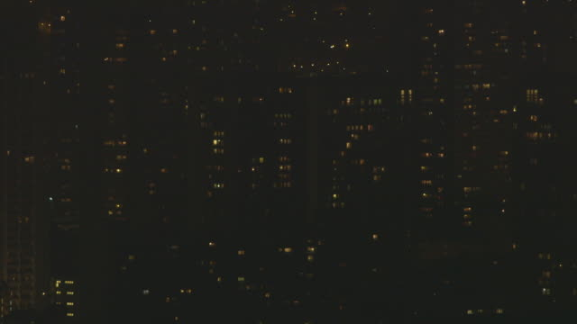 interspersed lights in the windows of faceless tower blocks slowly turn on, paris, france. - population explosion stock videos & royalty-free footage