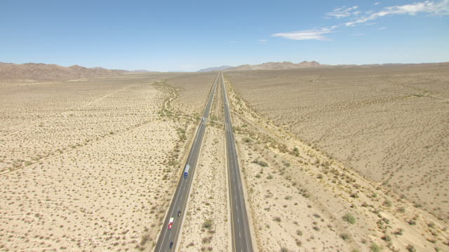 WS AERIAL POV Interstate 10 cutting across desert valley with foothills and mountain ranges in distance / California, United States