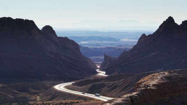 interstate 70 winding through dramatic utah landscape bisecting the san rafael reef - aerial shot - san rafael swell stock videos and b-roll footage