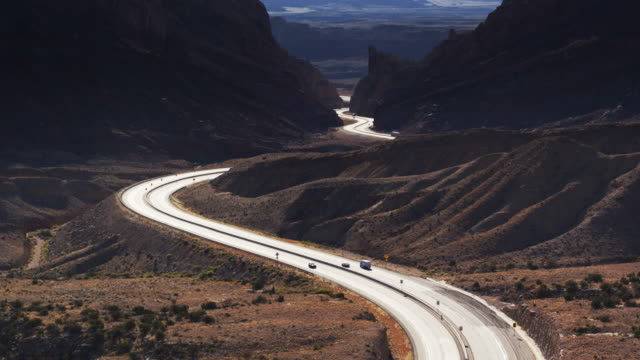 interstate 70 winding through dramatic utah landscape towards the san rafael reef - drone shot with upward tilt - san rafael swell stock videos and b-roll footage