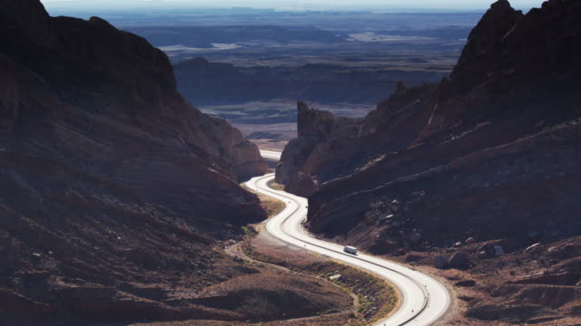 interstate 70 winding through dramatic utah landscape towards the san rafael reef - aerial shot - san rafael swell stock videos and b-roll footage