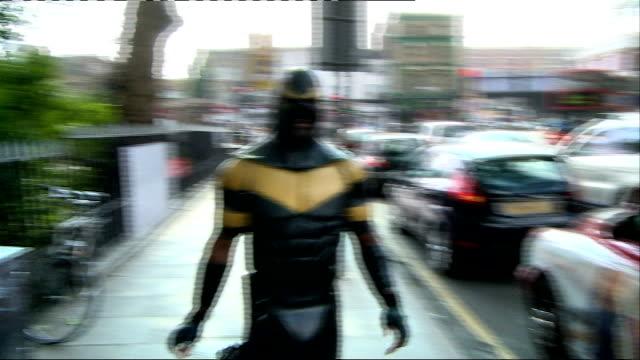 Interview with 'reallife superhero' Phoenix Jones ENGLAND London EXT People taking photographs of Phoenix Jones / Jones crossing road / TRACKING...