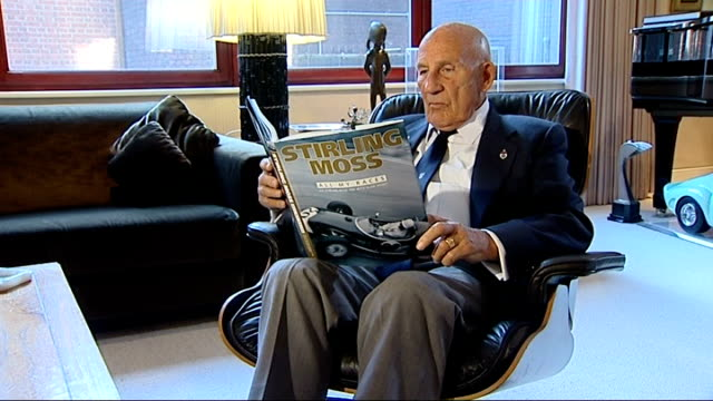 stockvideo's en b-roll-footage met interview with stirling moss moss reading glossy coffeetable autobiography nook - koffietafel