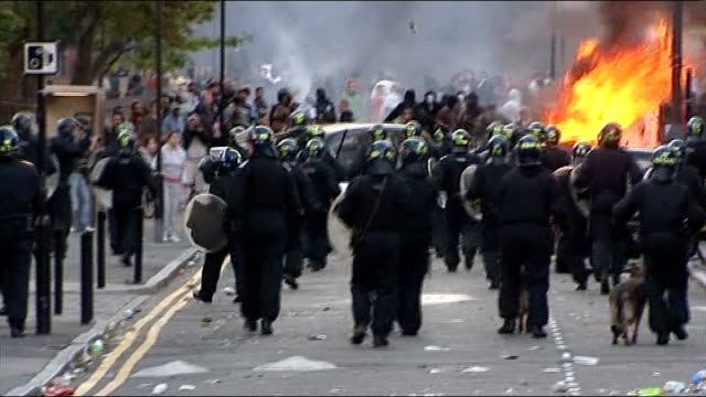 interview with the bishop of london about 2011 august 2011 london ext riot police along street with burning car and rioters in distance - bishop of london stock videos & royalty-free footage