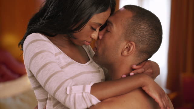 intimate african couple kiss sensually privately in bedroom - afrikanischer abstammung stock-videos und b-roll-filmmaterial