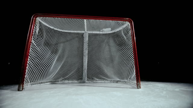 SLO MO DS Into the goal's net in ice hockey rink