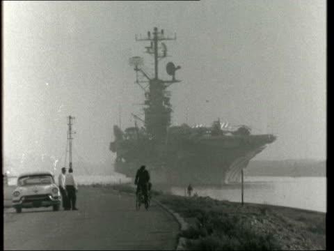 intrepid' sails through suez canal; egypt: suez canal: gv us 'intrepid' along suez canal - man rides bicycle at side: neg: 16mm: itn: 8ft: 12secs:... - suez canal stock videos & royalty-free footage