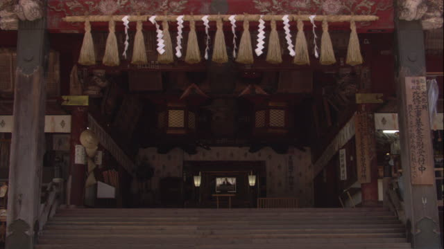 intricate carvings and a shimenawa rope adorn the entrance of a shinto shrine. - shimenawa stock videos & royalty-free footage