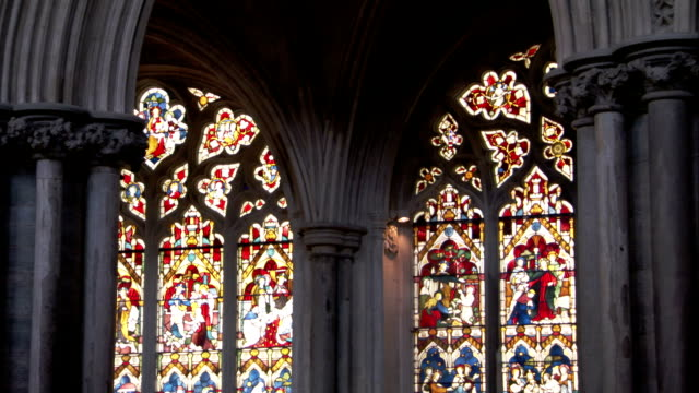 vídeos de stock e filmes b-roll de intricate stained glass windows illuminate the interior of the ely cathedral. available in hd. - idade media