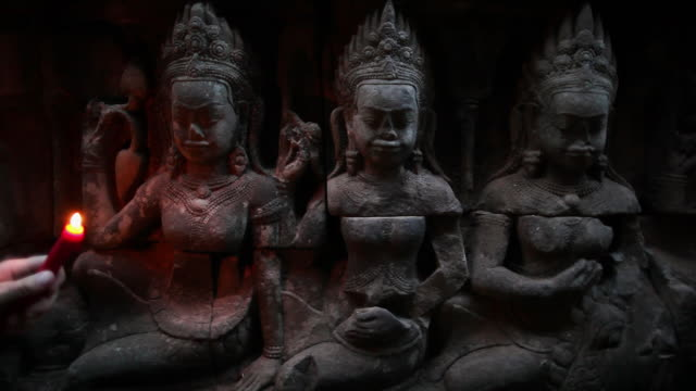 cu intricately carved stone figures lit by candlelight in an ancient temple in angkor wat / siem reap, cambodia - god stock videos & royalty-free footage