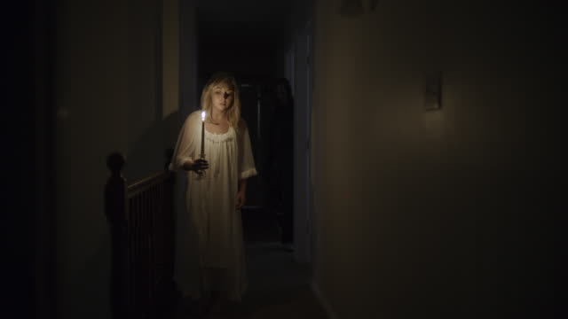 vidéos et rushes de intruder sneaking behind woman in nightgown investigating home with candle / springville, utah, united states - springville utah