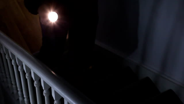 intruder with flashlight on stairs. - electric torch stock videos & royalty-free footage