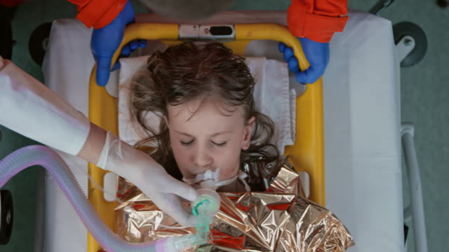 stockvideo's en b-roll-footage met intubated hypothermic child in a thermal blanket on breathing support - eerste hulp