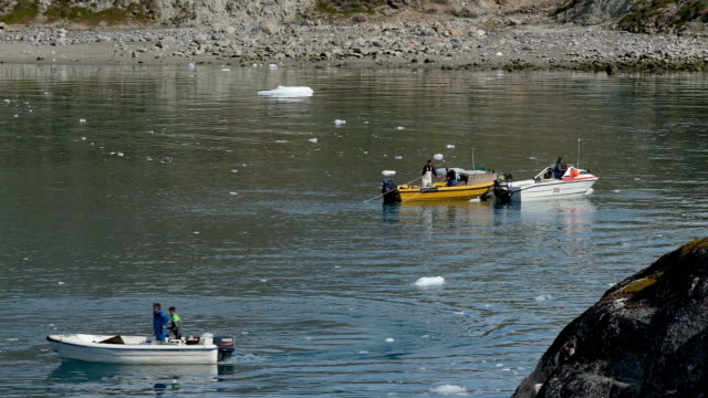 inuit fishermen prepare a net as freefloating ice floats behind at the mouth of the ilulissat icefjord during unseasonably warm weather on july 30... - inuit stock videos & royalty-free footage