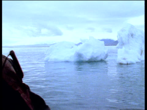 inuit man in boat glides by icebergs arctic - inuit stock videos & royalty-free footage
