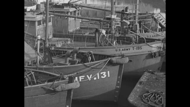 VS invasion crafts at British dock including landing crafts battleships boats and ships some vessels are marked 'US Army' / VS black men hammer...