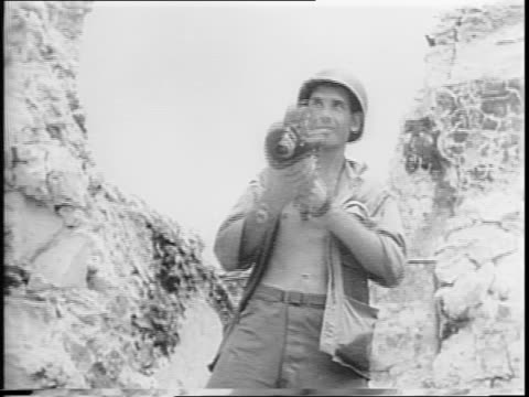 Invasion of Palau Island / Paramount cameraman Damien Parer standing with camera / Parer killed while shooting this battle / marines in action...