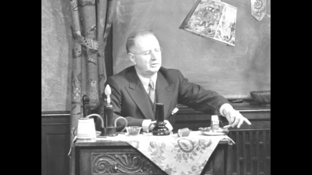 inventor dr william j mccormick sits at table with electric smoking devices which resemble hookahs sot he explains how his device works through... - 発明家点の映像素材/bロール