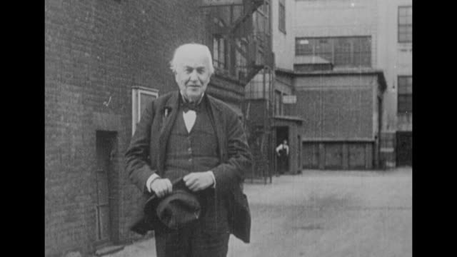 Inventor Thomas Edison approaches camera as he walks in alleyway he bears a slight smile this is probably from the mid1920s / Note exact year not...