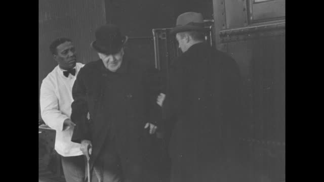 Inventor Thomas Edison is helped from a passenger train by an AfricanAmerican porter as he returns to New Jersey after appearing at the Henry...