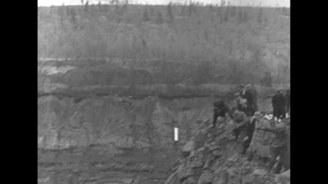 inventor william kirst talks to camera about tests of du pont's new explosive nitramon / men standing next to edge of large strip mine hole one man... - plunger stock videos and b-roll footage