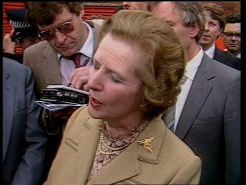 Inverness MS Prime Minister Margaret Thatcher in tartan factory machines towards LMS Thatcher looking in ream of tartan BV Thatcher trying on tartan...