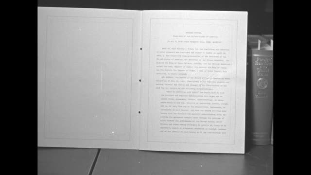inverted shot of us naval treaty document standing in front of legal books on shelf / cu document ratifying the treaty for the limitation and... - facciata video stock e b–roll