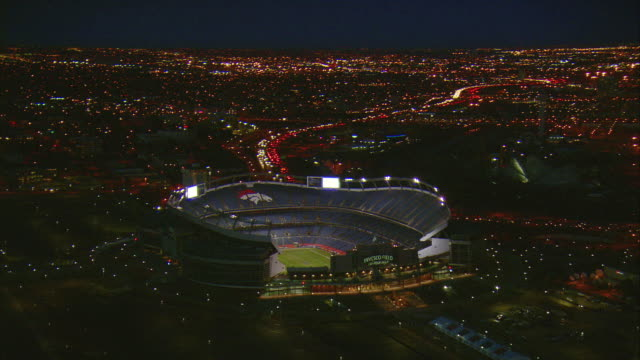 ws pan zo aerial invesco field with downtown denver skyline / denver, colorado, usa - floodlight stock videos & royalty-free footage