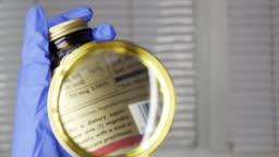 Investigating ingredients of medicines, chemicals used in pills capsules inside box using magnifying glass, gloved hand