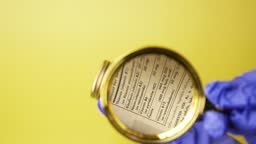 Investigating ingredients of medicines, chemicals used in pills capsules inside box using magnifying glass on yellow background, gloved hand