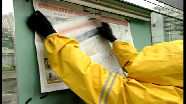 investigation into 10 years of change ext man in yellow jacket places pages from official communist party newspaper into display case people reading... - communist party stock videos and b-roll footage