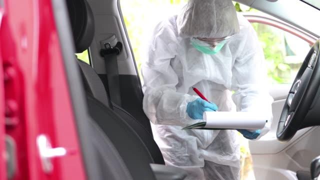 犯罪現場に関するメモを取る防護服の捜査官 - 犯行現場点の映像素材/bロール