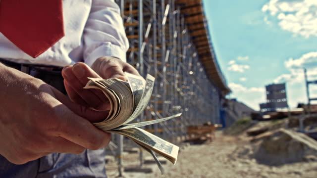 slo mo investitore conto in contanti presso il cantiere di costruzione - banconota da 10 dollari statunitensi video stock e b–roll