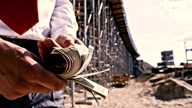 slo mo investitore conteggio del denaro alla costruzione sito - banconota da 10 dollari statunitensi video stock e b–roll