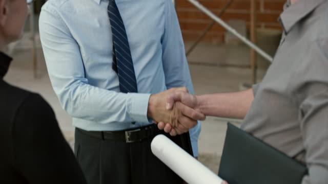 investor händeschütteln mit zwei architekten außerhalb auf der baustelle - hemd und krawatte stock-videos und b-roll-filmmaterial