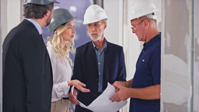 pan investors, a man and woman, discussing the plans with construction supervisor and architect - blonde hair stock videos & royalty-free footage