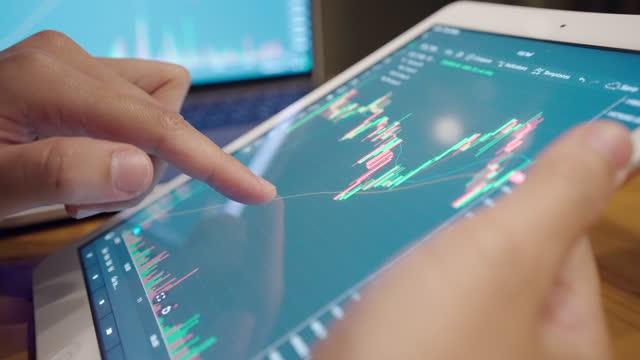vídeos de stock, filmes e b-roll de os investidores estão negociando ações. no mercado eletrônico através do computador pela internet via celular. - perícia