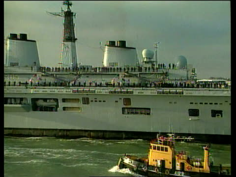 portsmouth ext pan along ms hms invincible with naval crew standing in line along deck pull out to bv relatives waving them off on board ship tbv... - marine stock-videos und b-roll-filmmaterial