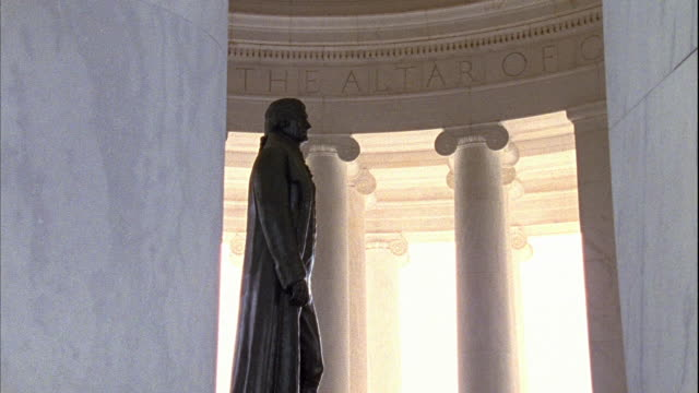 ionic columns of thomas jefferson memorial revealing statue standing in center of portico w/ declaration of independence preamble carved on wall... - thomas jefferson stock videos & royalty-free footage