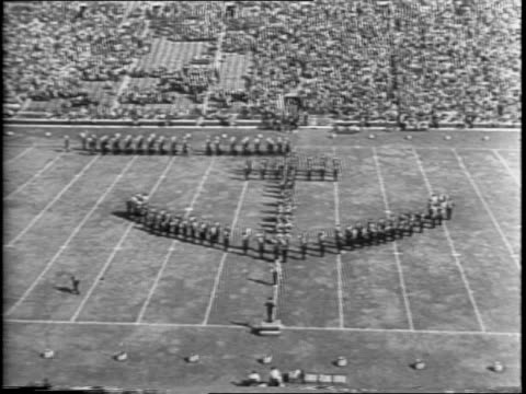 iowa preflight seahawks play against michigan wolverines in a 1942 college football match at michigan stadium / cadets in anchor formation on field /... - anno 1942 video stock e b–roll