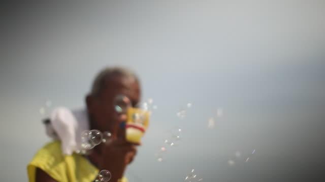 vídeos de stock, filmes e b-roll de ipanema beach, beach seller blows bubbles - sc47
