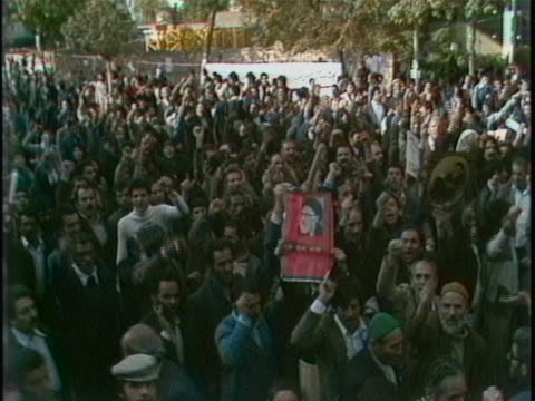 vídeos de stock e filmes b-roll de iran street crowd chanting and holding english sign 2 there is an opening medium shot of a crowd of people holding signs and papers while chanting... - street name sign