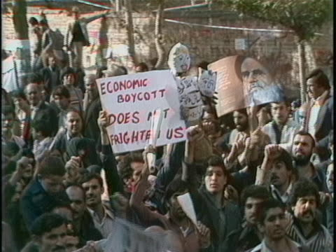 vídeos de stock e filmes b-roll de iran street crowd chanting and holding english sign there is an opening medium shot of a crowd of people holding signs and papers while chanting... - street name sign