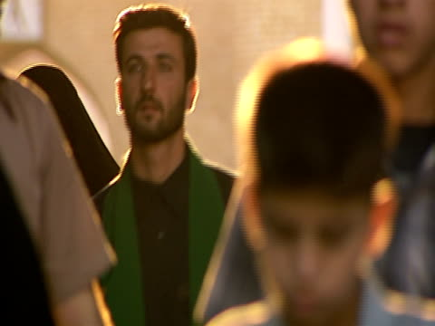 vidéos et rushes de iranian citizens walking through an arched doorway at qom shrine / qom, iran - format vignette