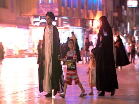 vidéos et rushes de iranian family walking at night in a plaza / qom, iran - format vignette