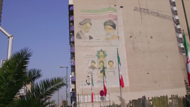 iranian flags and a wall mural depicting martyrs as well as ayatollah ali khamenei irans supreme leader left and ruhollah khomeini founder of the... - イラン点の映像素材/bロール