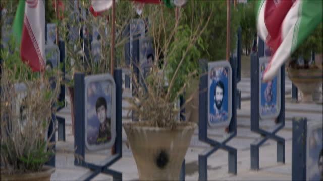vídeos de stock e filmes b-roll de cu tu iranian flags blowing in wind at iraq war cemetery, esfahan, iran - figura masculina