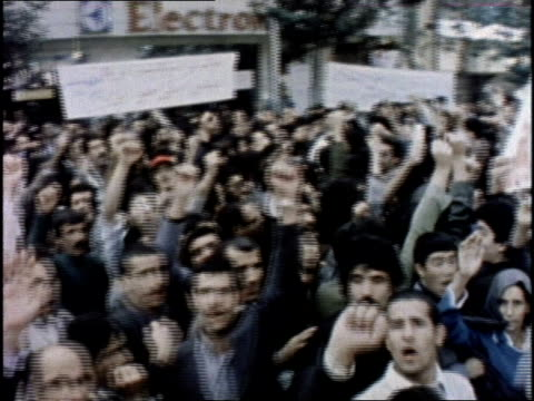 Iranian protesters shout and raise their fists during a political demonstration in Tehran
