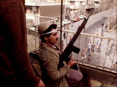 vídeos de stock, filmes e b-roll de imperial palace falls to supporters of the ayatollah khomeini ts crowd at wall pan barracks burning ms fighter with rifle on balcony pan barracks... - irã